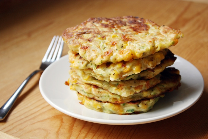 stack of zucchini corn pancakes on plate with fork