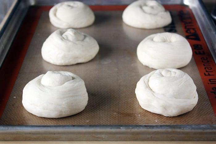 brioche hamburger buns on baking sheet ready to go in oven