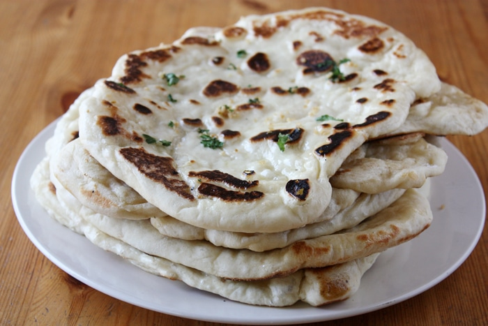 garlic butter naan stacked on plate
