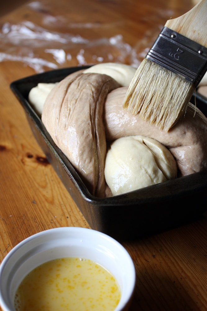 egg washing the braided rye dough