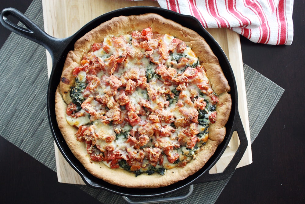 deep dish spinach tomato pizza in cast iron skillet