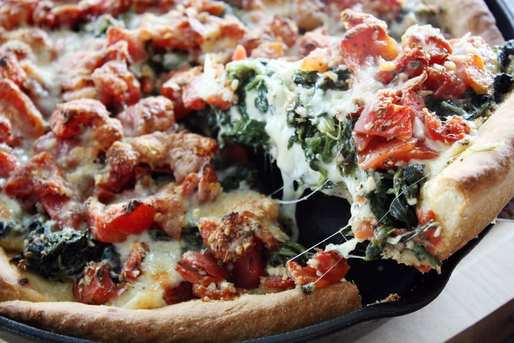 close up deep dish spinach tomato pizza slice