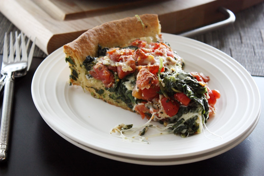 slice of deep dish spinach tomato pizza on a plate