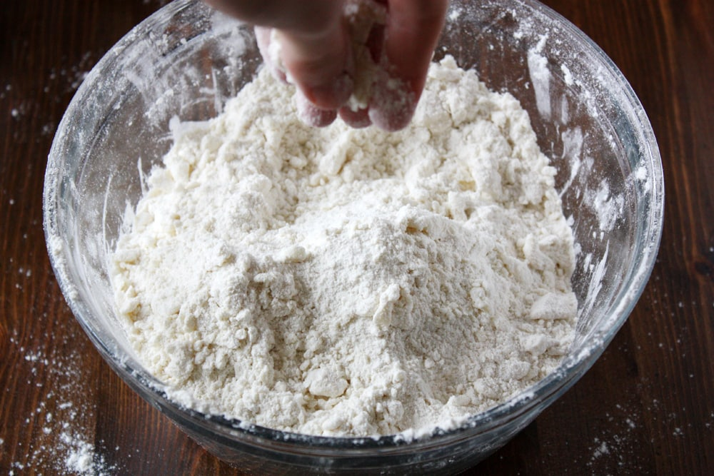 mixing ingredients for powdermilk biscuit dough in bowl
