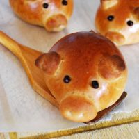 sausage stuffed piglet bun on wooden spoon