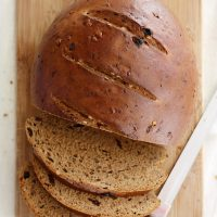 raisin walnut pumpernickel bread loaf on cutting board