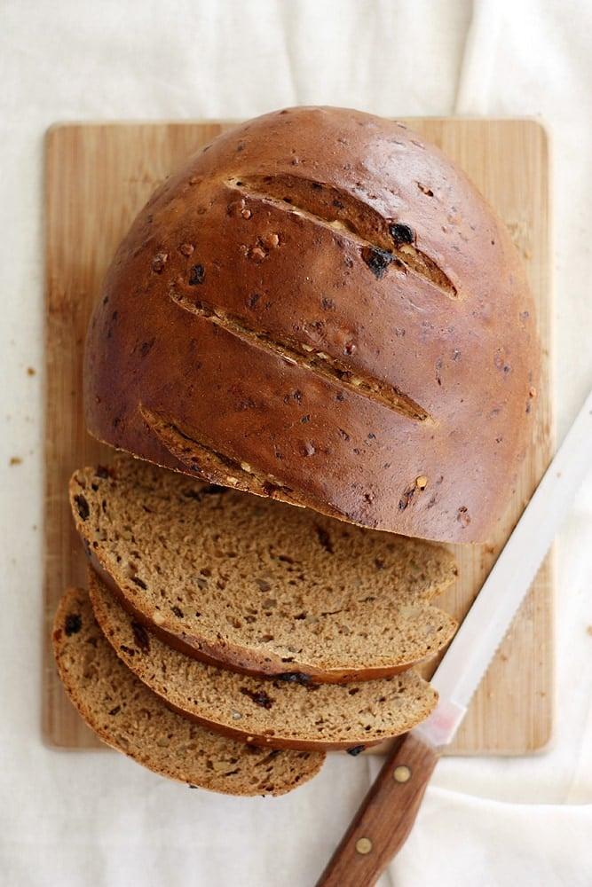 raisin walnut pumpernickel bread loaf on cutting board