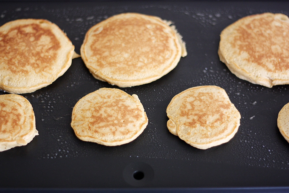 pancakes being cooked on griddle