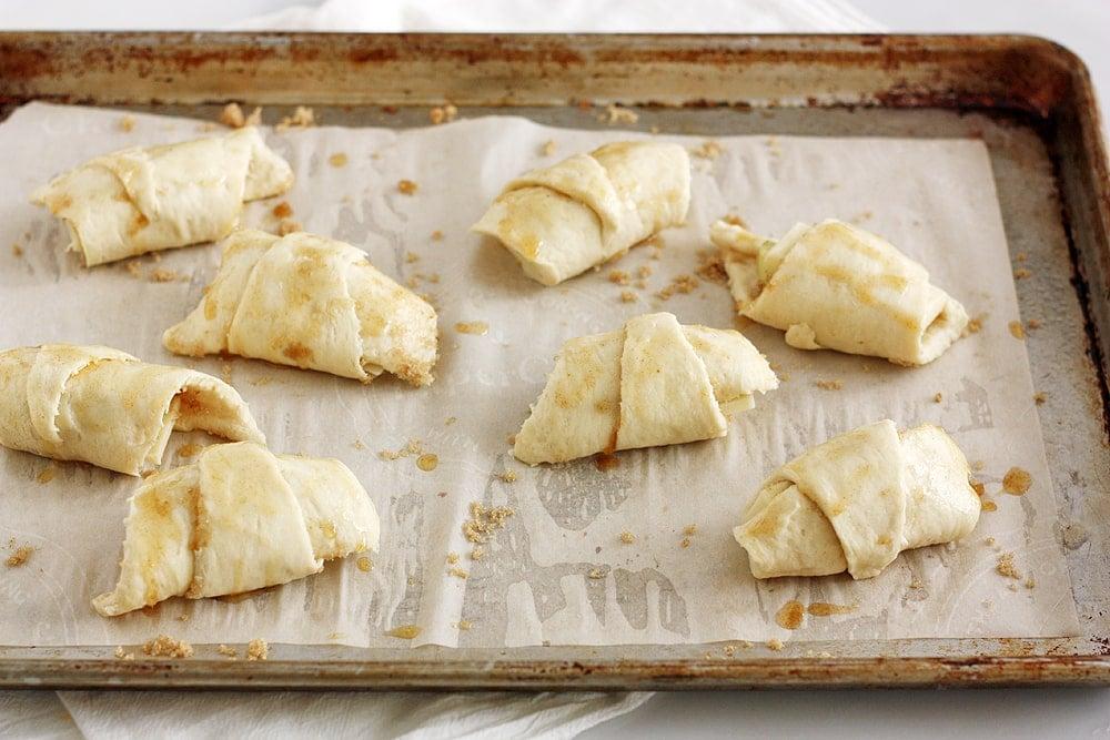 preparing brown butter apple cheddar pie crescent rolls on baking sheet