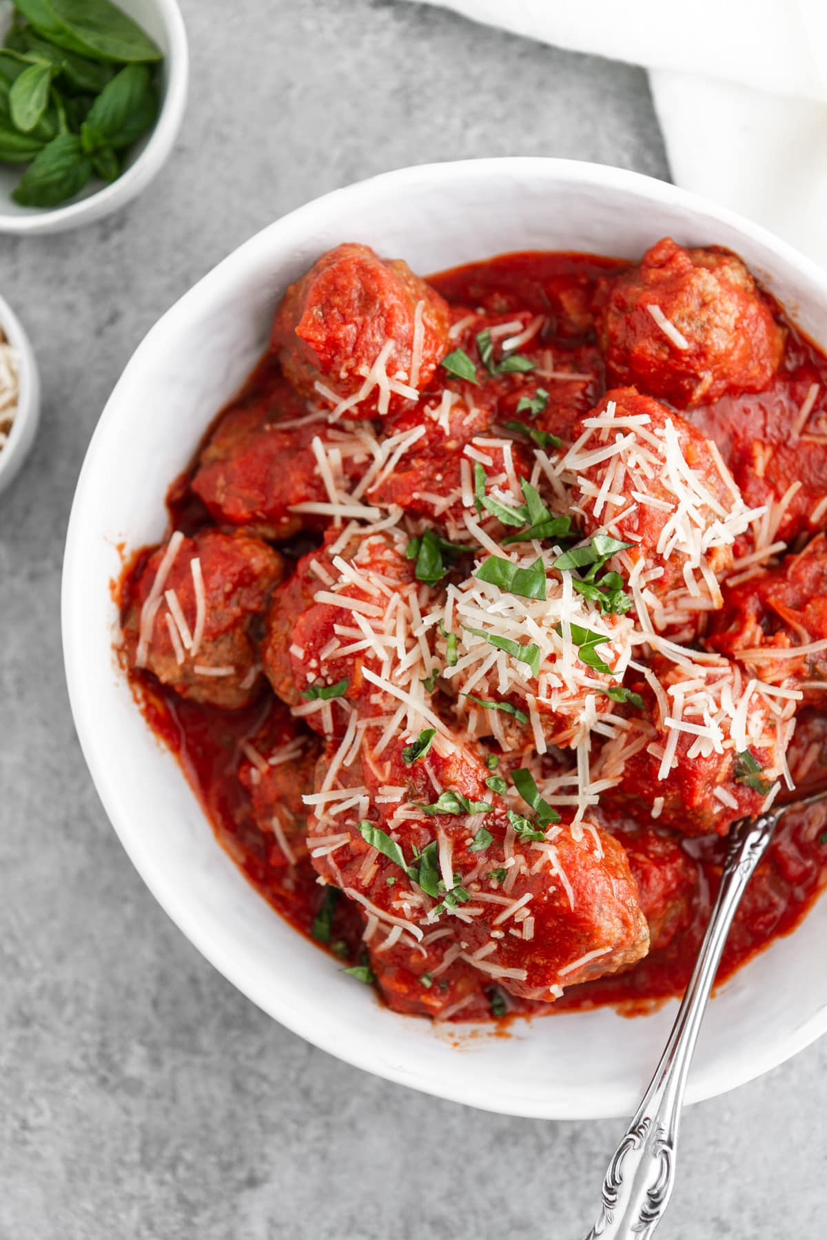 slow cooker italian meatballs in a bowl with cheese and basil on top