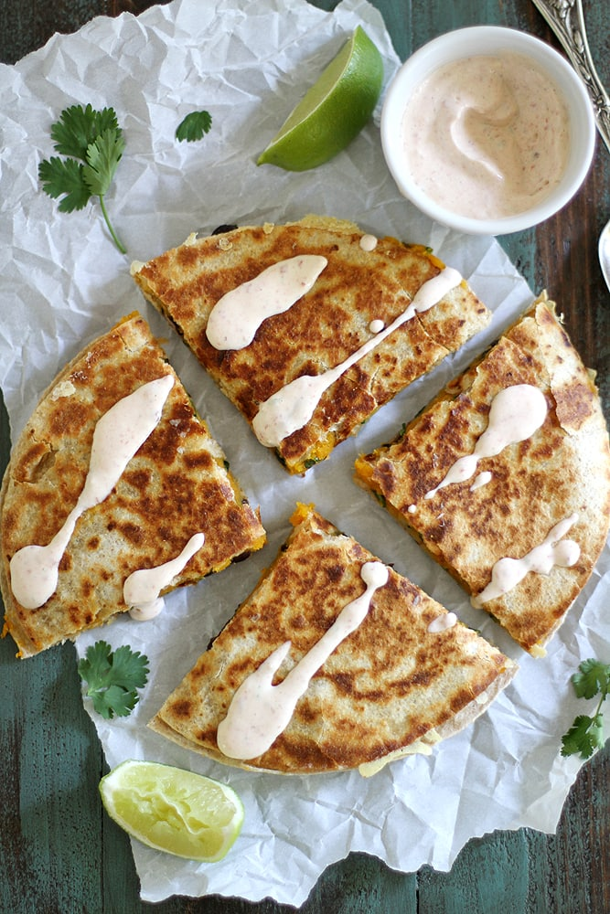 quesadilla on parchment paper with crema drizzled