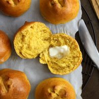 sliced pumpkin brioche roll with pat of butter