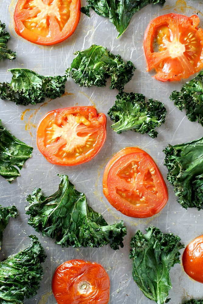 roasted tomatoes and kale on a baking sheet