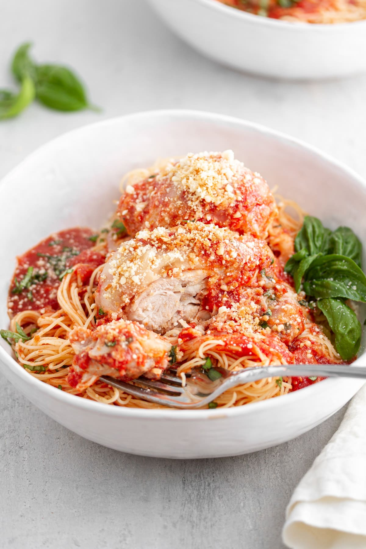 bowl of slow cooker chicken parmesan with chicken cut by fork