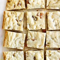 sliced apricot white chocolate brownies on parchment paper