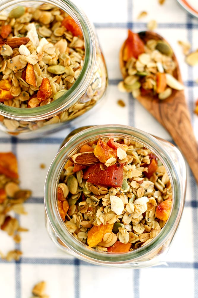 ginger peach granola in glass jar on kitchen towel