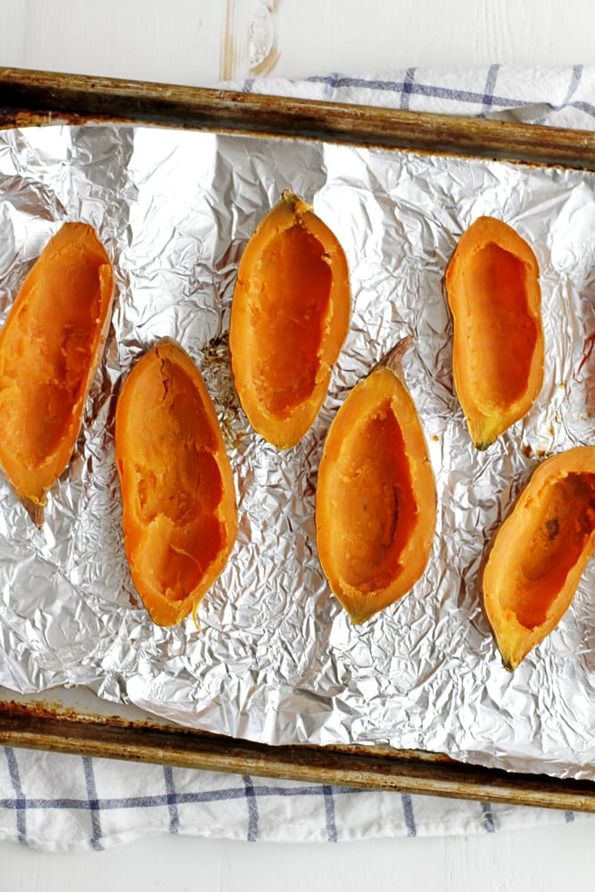 scooped out sweet potatoes on foil in baking sheet