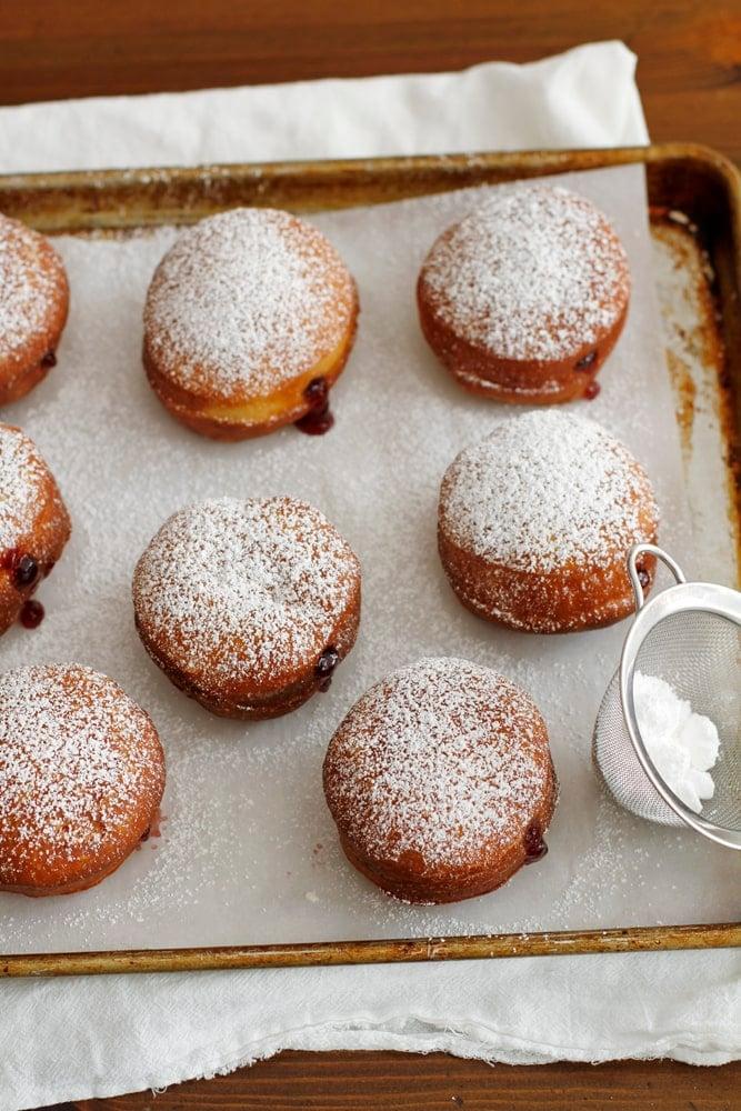 sprinkling powdered sugar on doughnuts
