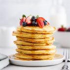 stack of coconut flour pancakes on a plate with berries on top