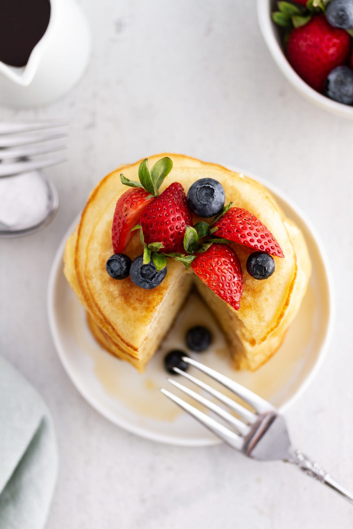 an overhead shot of a stack of coconut flour pancakes on a plate topped with berries
