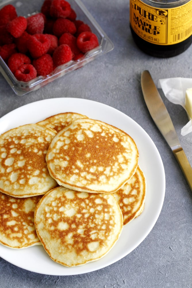 plate of fluffy coconut flour pancakes with raspberries and butter on the side