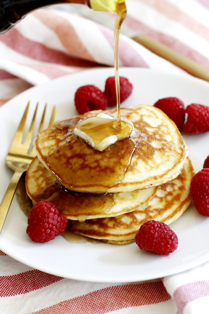syrup poured on a plate of fluffy coconut flour pancakes