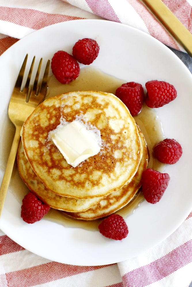 plate of fluffy coconut flour pancakes with syrup and raspberries