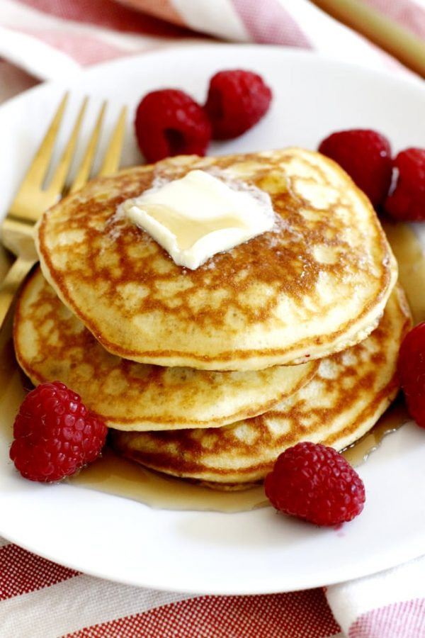 stack of fluffy coconut flour pancakes with syrup and raspberries