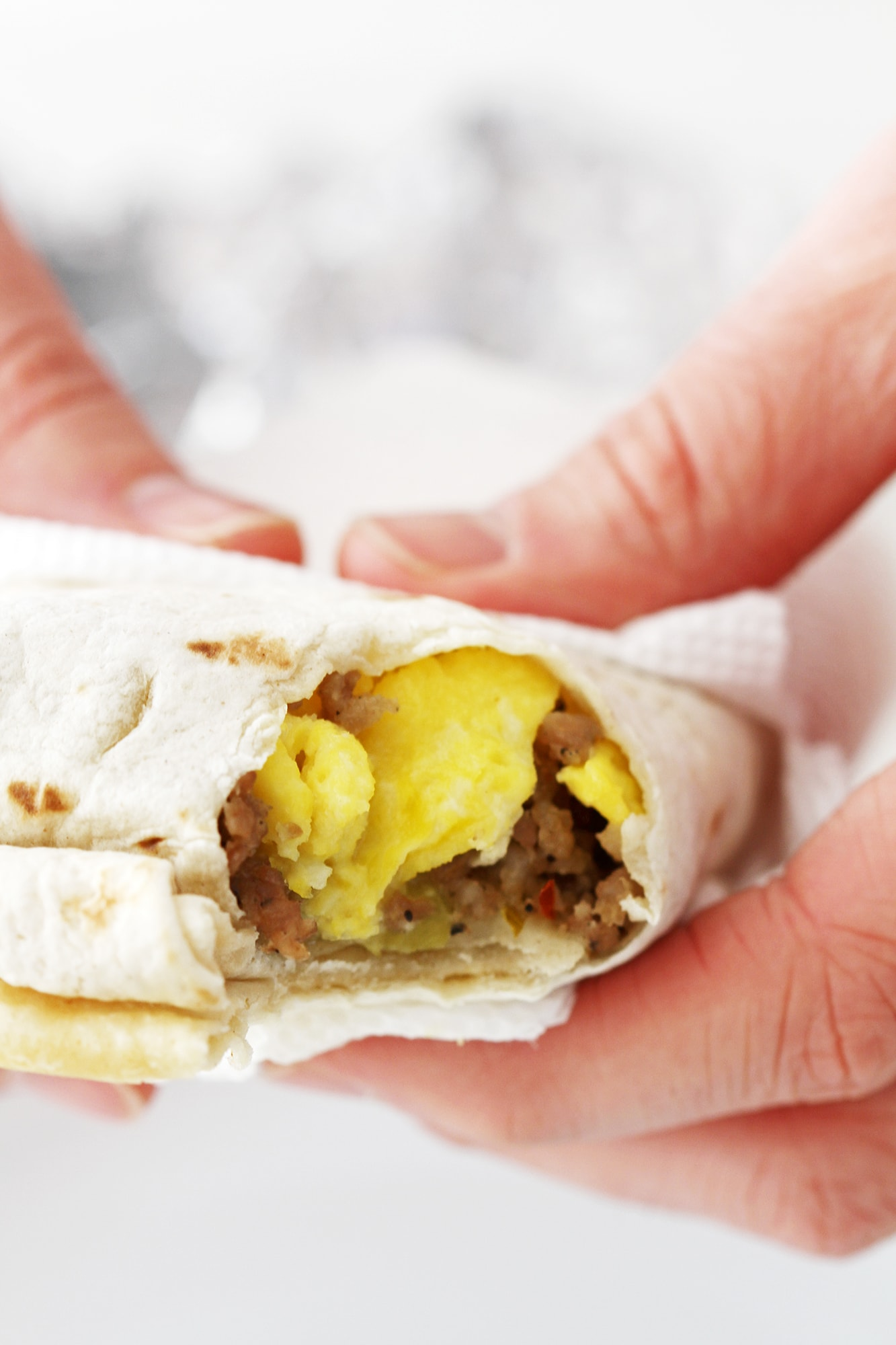 hands holding a freezer breakfast burrito