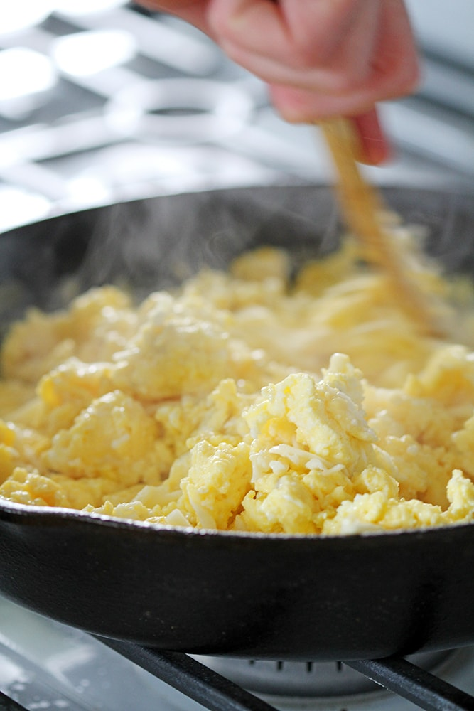 cooking scrambled eggs in cast iron skillet on stove