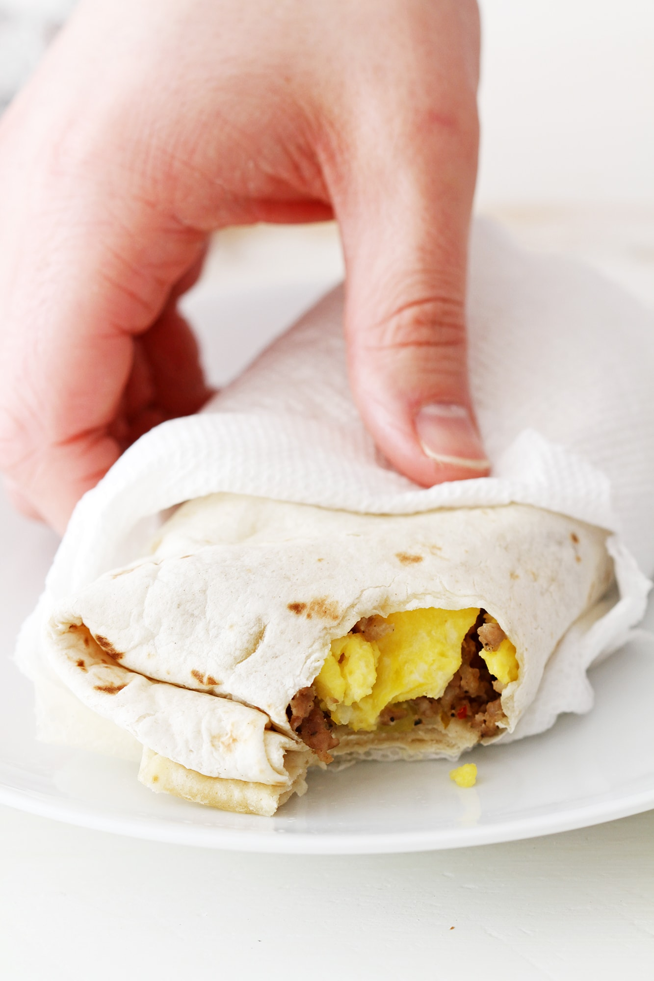 hand holding freezer breakfast burrito with bite taken