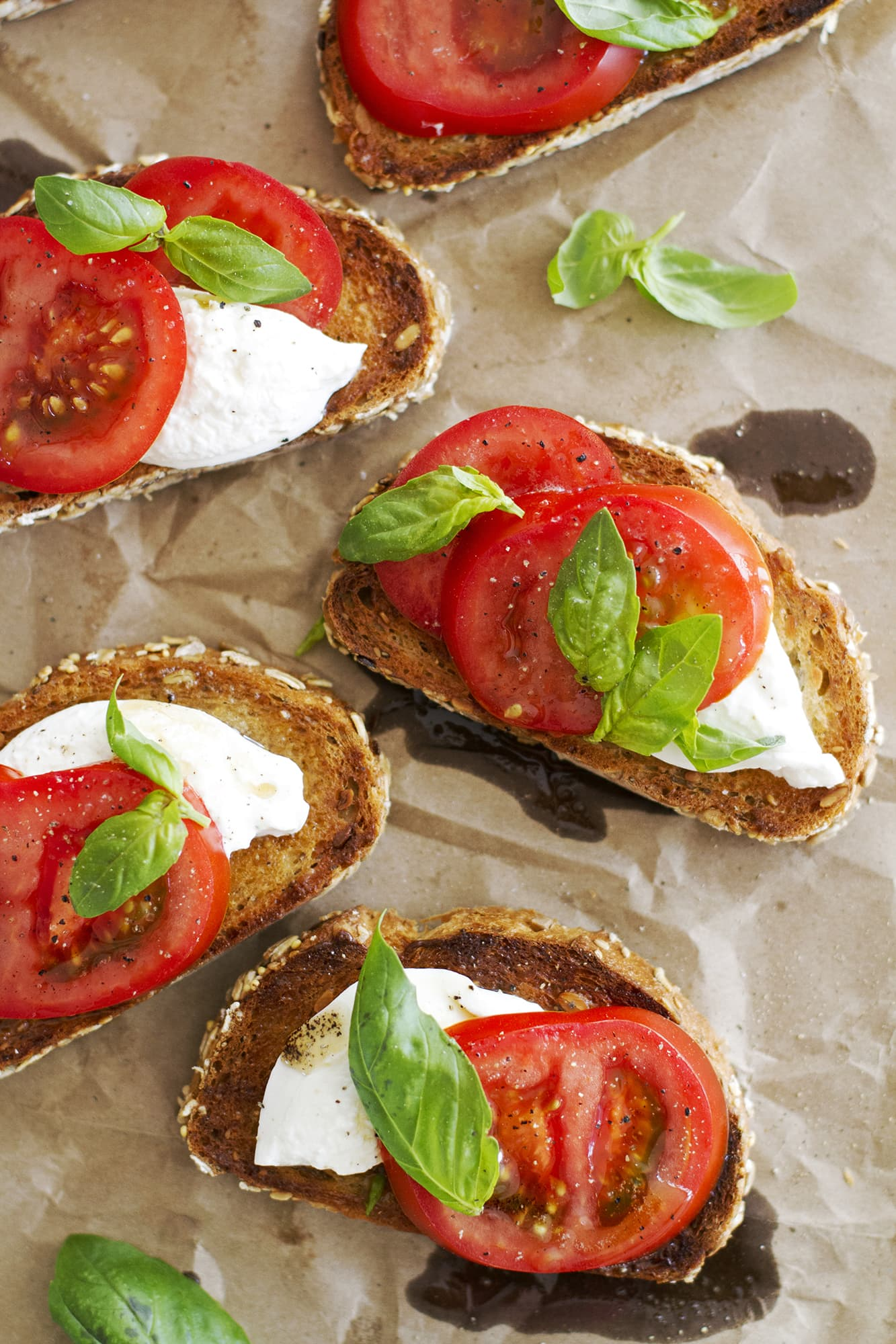 caprese sandwiches with burrata on parchment paper