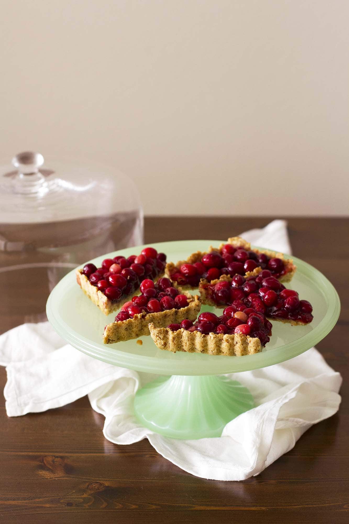 nut crusted cranberry tart on cake stand