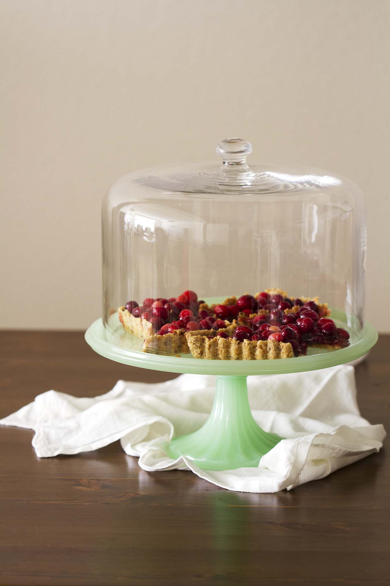 nut crusted cranberry tart on glass covered cake stand