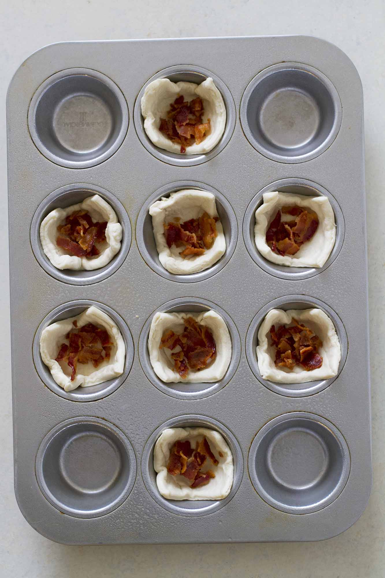 filling crescent cups with bacon