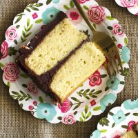 slice of classic yellow cake with chocolate buttercream frosting