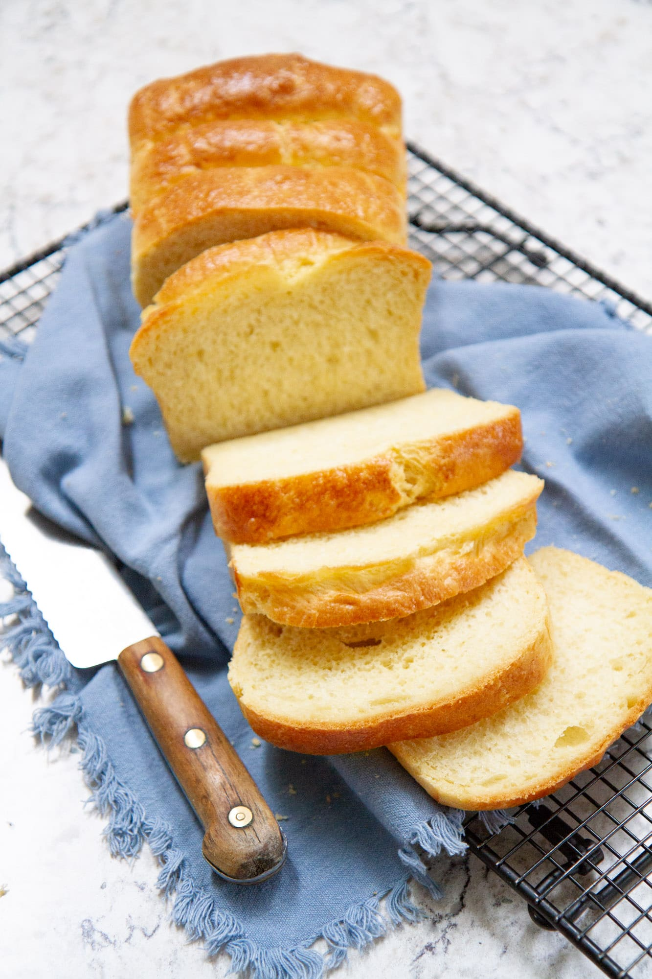 classic brioche loaf bread sliced on cooling rack