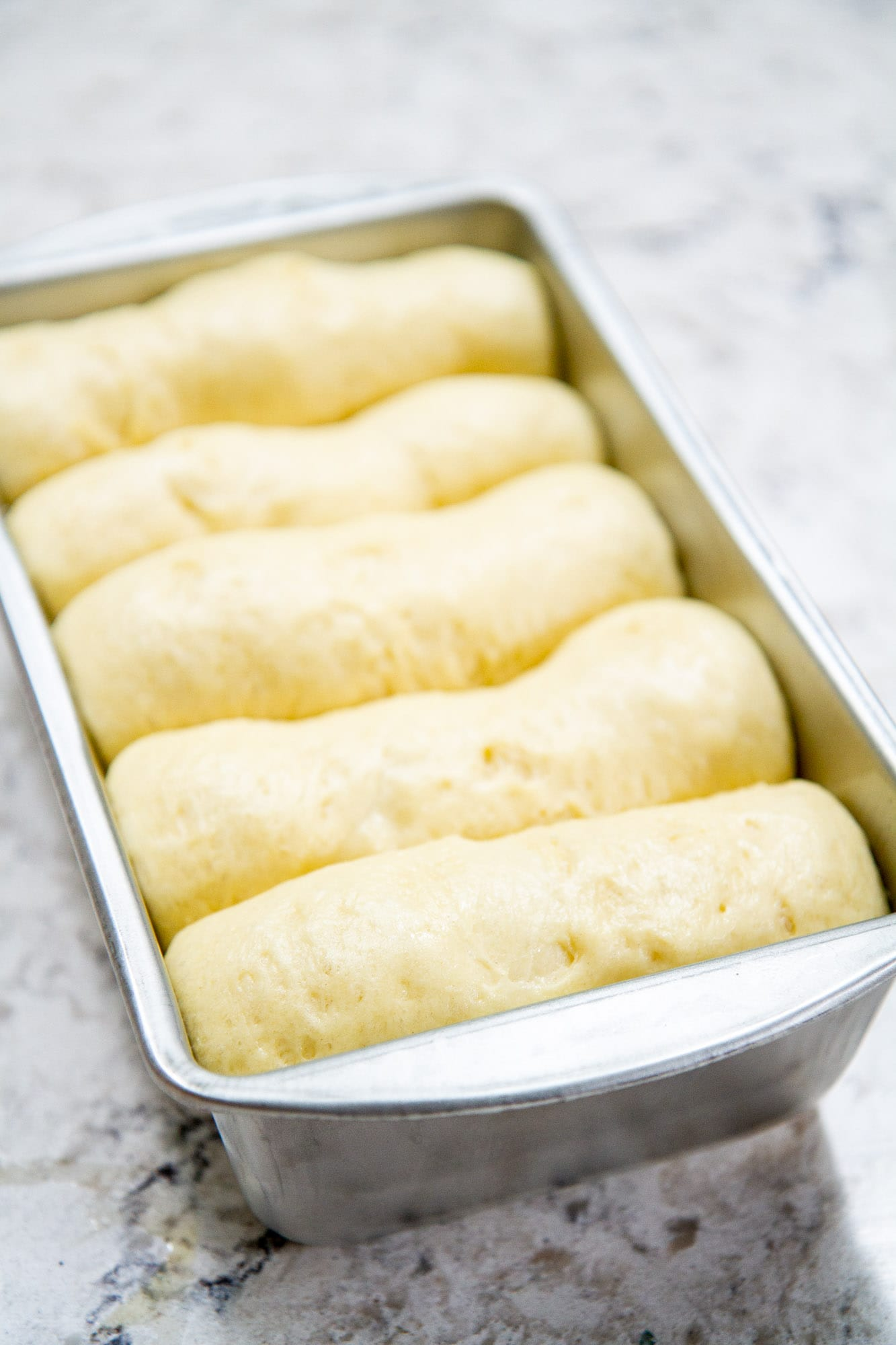 risen classic brioche loaf bread in baking pan