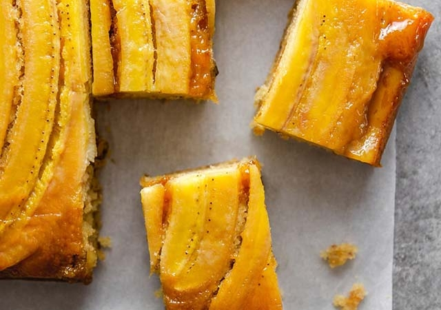 slices of bananas foster upside-down cake on parchment paper