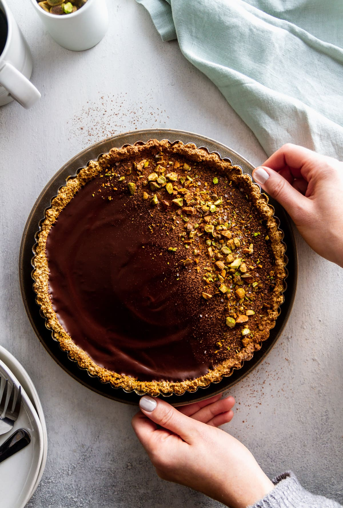 hands placing a chocolate tart on a surface