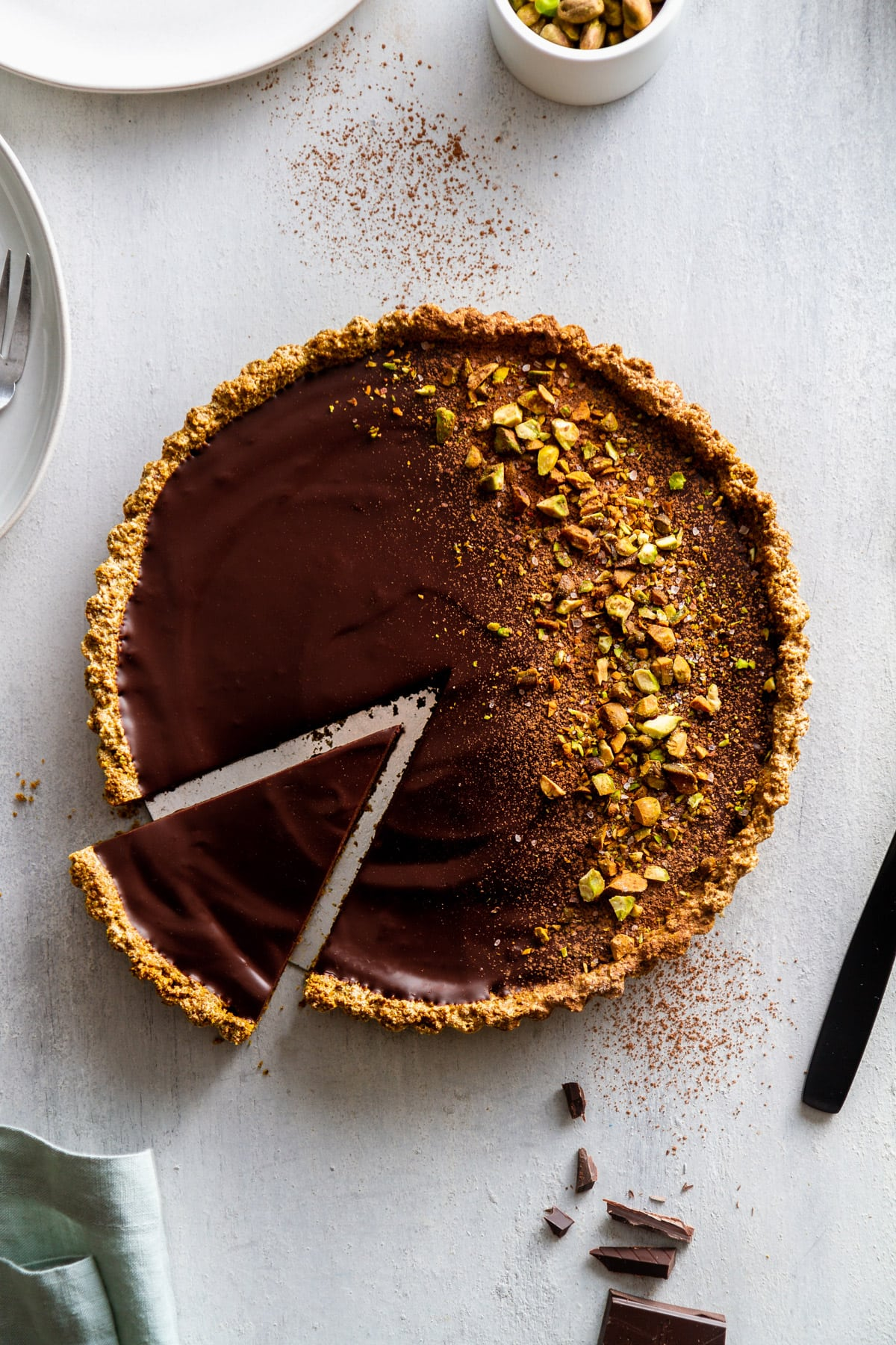 a dark chocolate pistachio tart with a slice out of it on a surface
