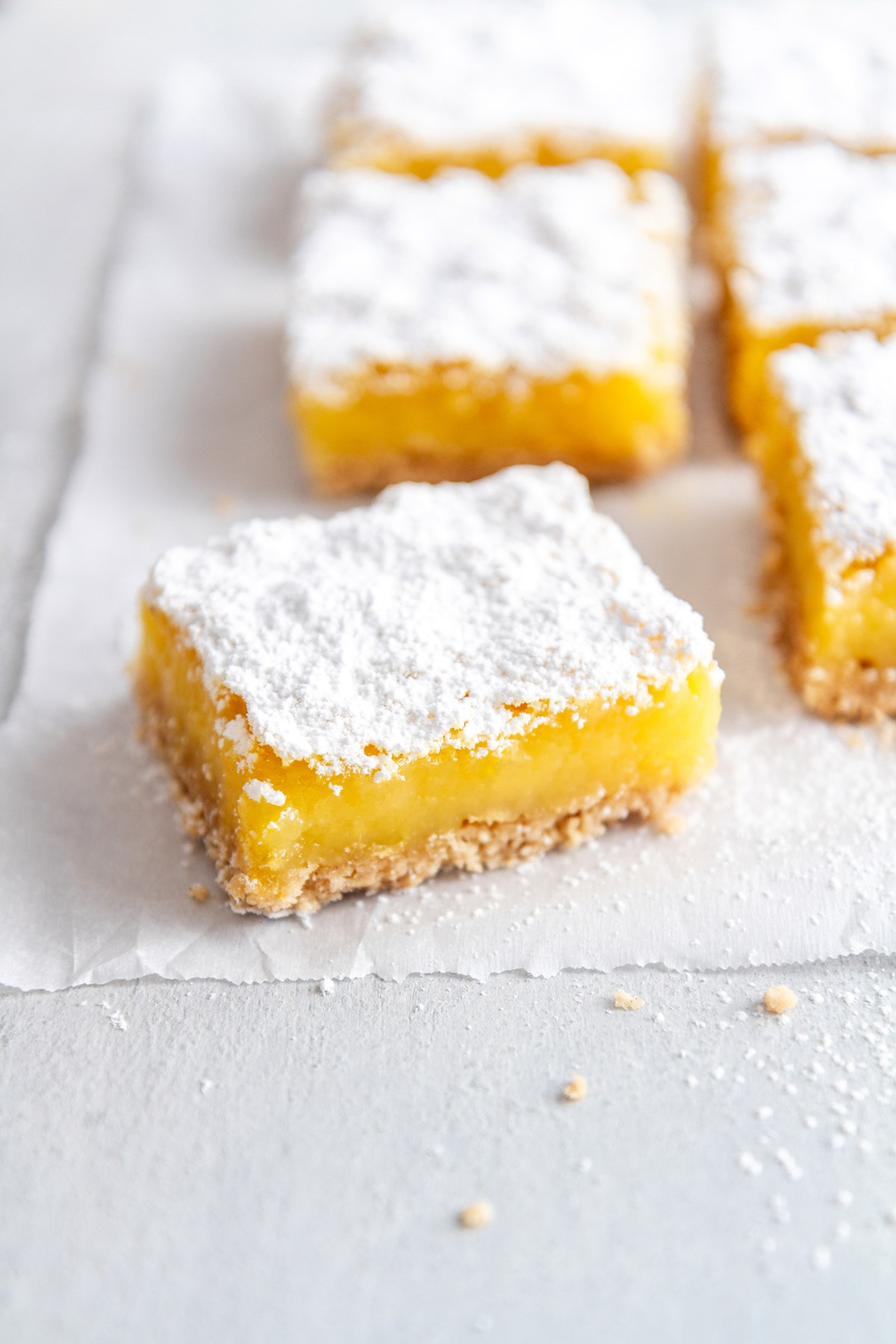 a gluten free lemon bar on a sheet of parchment paper