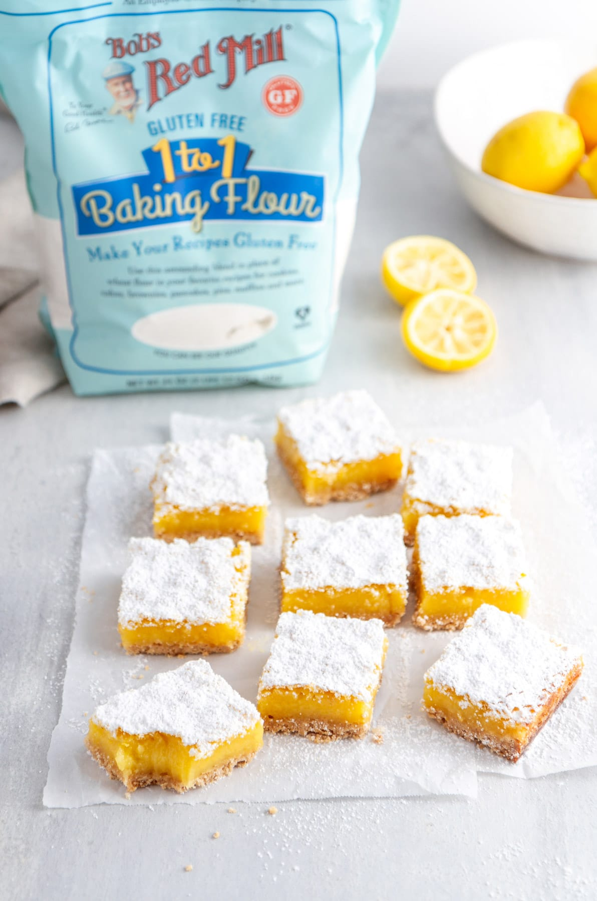 lemon bars on parchment paper with gluten free flour in the background