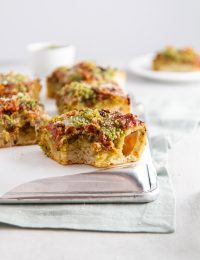 Winter Deep Dish Sausage Pizza with Brussels Sprouts and Pesto Recipe -- Homemade no-knead pizza dough topped with sauteed Brussels sprouts, bright pesto, melty mozzarella cheese and hot Italian sausage. This easy pizza recipe will keep you full and cozy all winter long. @girlversusdough #girlversusdough #weeknightdinner #datenightrecipe #winterrecipe