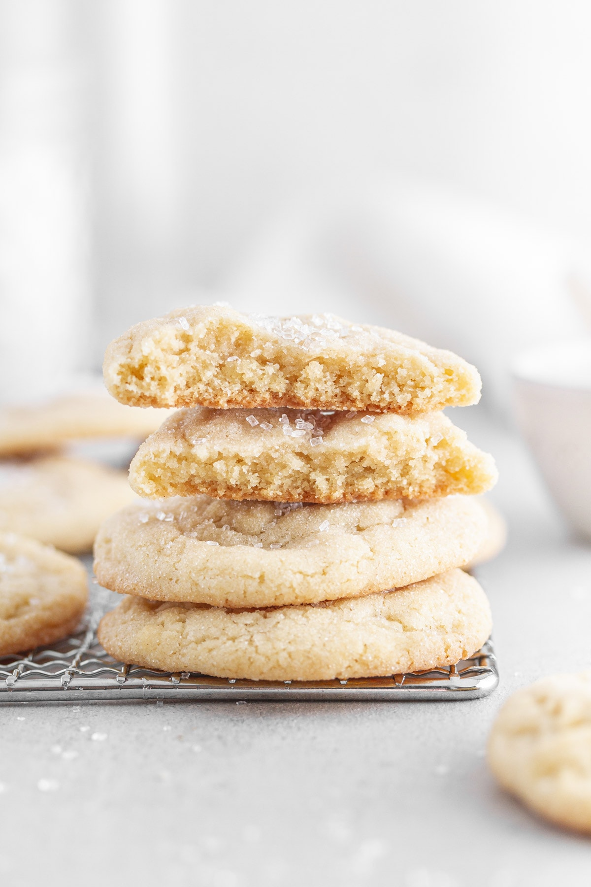 chewy sugar cookies stacked on top of each other on a cooling rack