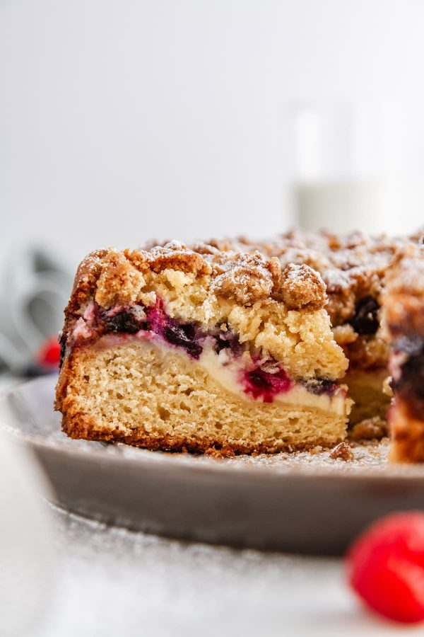 a close-up shot of a slice of berry cream cheese coffee cake