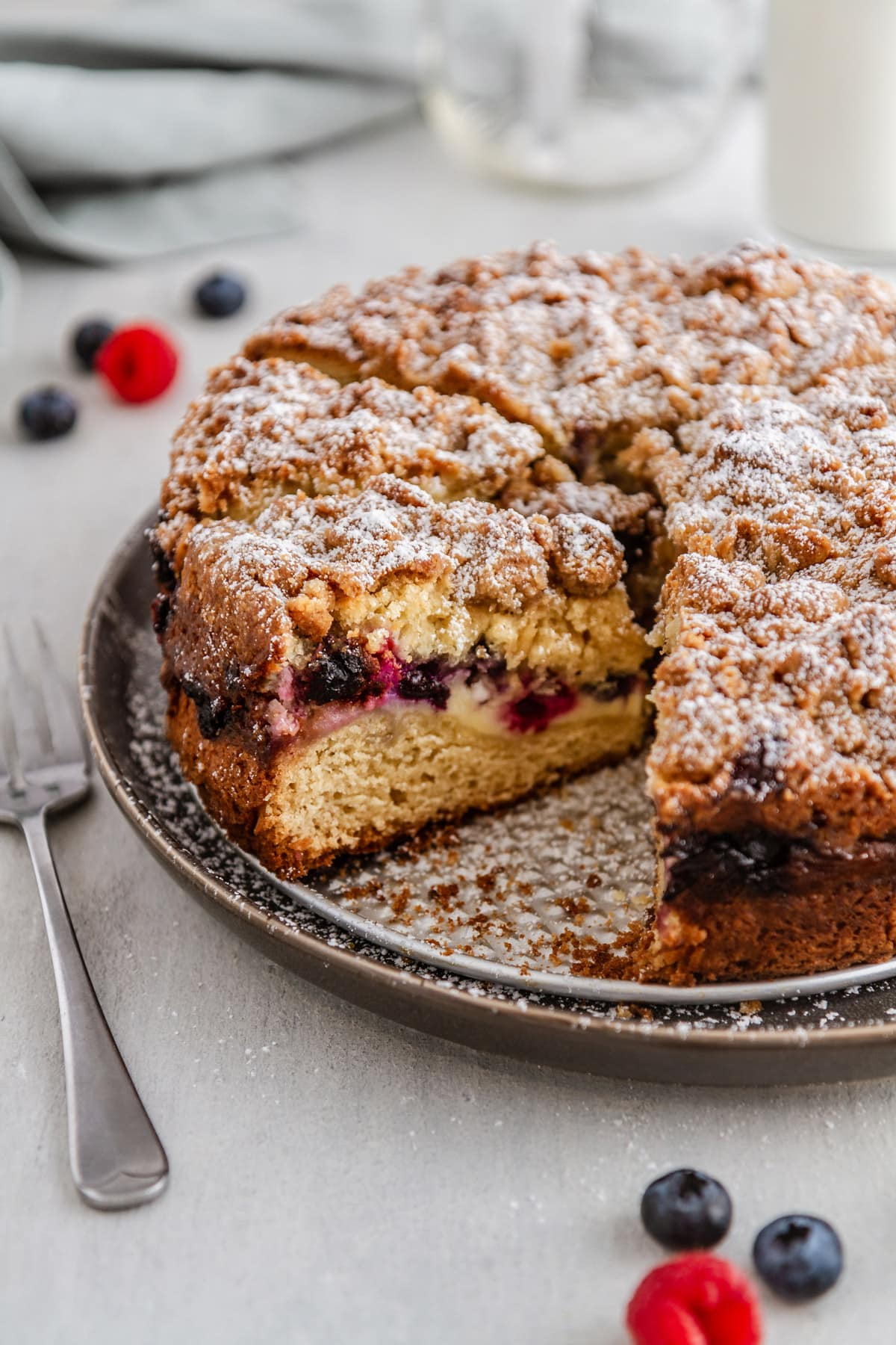 a slice of berry cream cheese coffee cake on a plate with a fork next to it