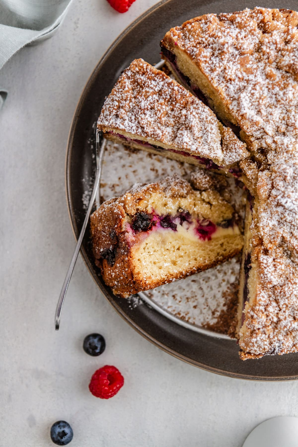 an overhead shot of a slice of berry cream cheese coffee cake
