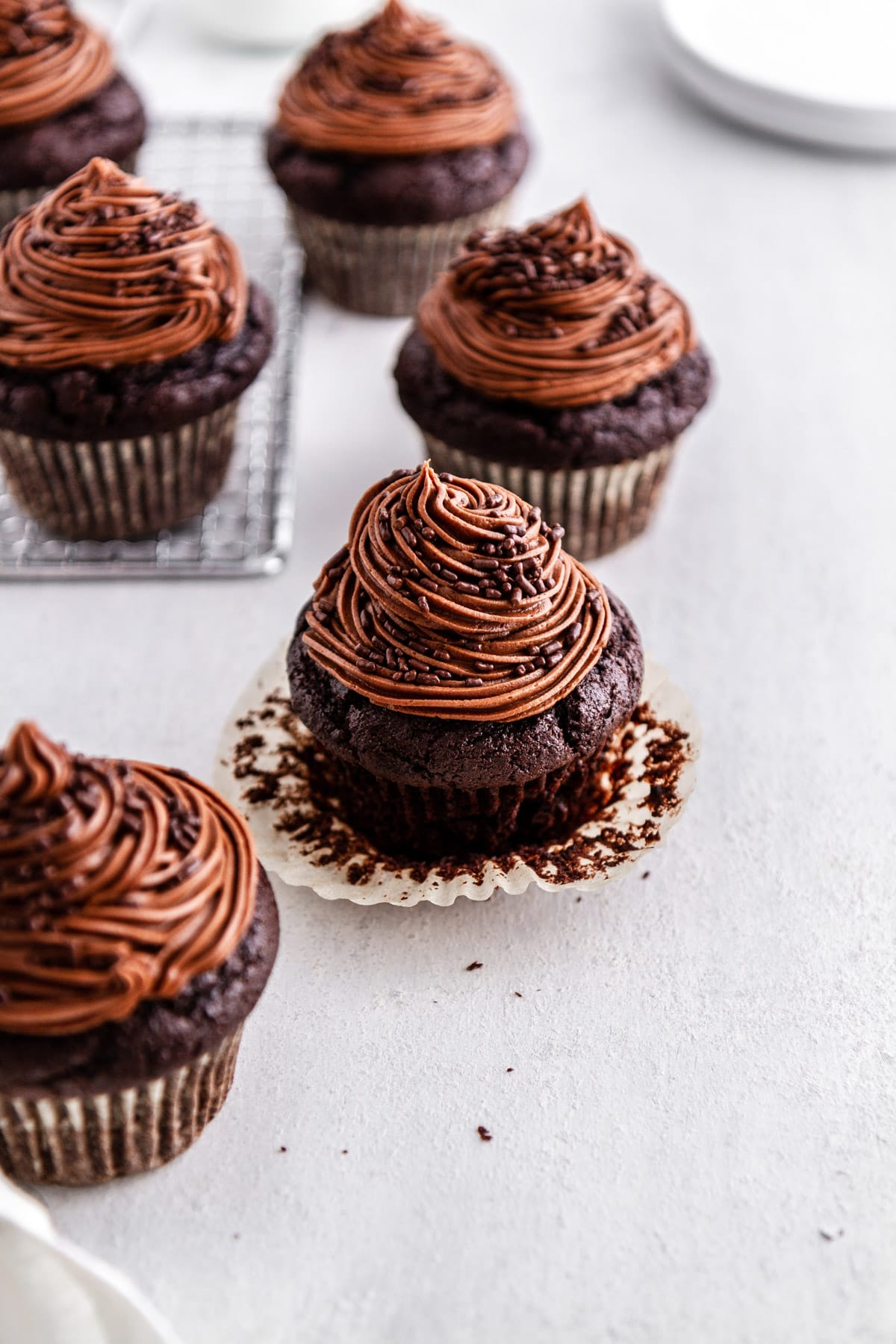 chocolate cupcakes on a cooling rack and on a surface