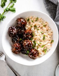 korean bbq meatballs in a bowl with rice with fork off to the side
